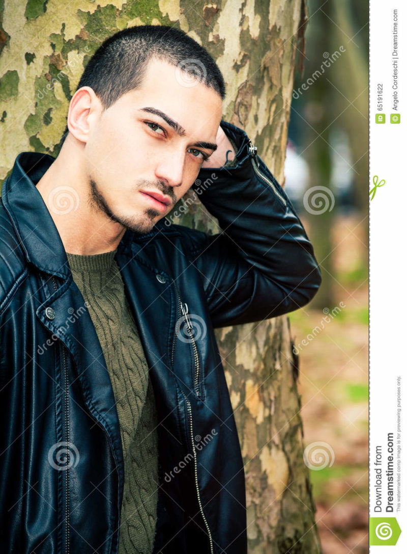 Man portrait outdoors. Handsome natural male Portrait of a young handsome man near a tree. Intense gaze and eye-catching. Italian man