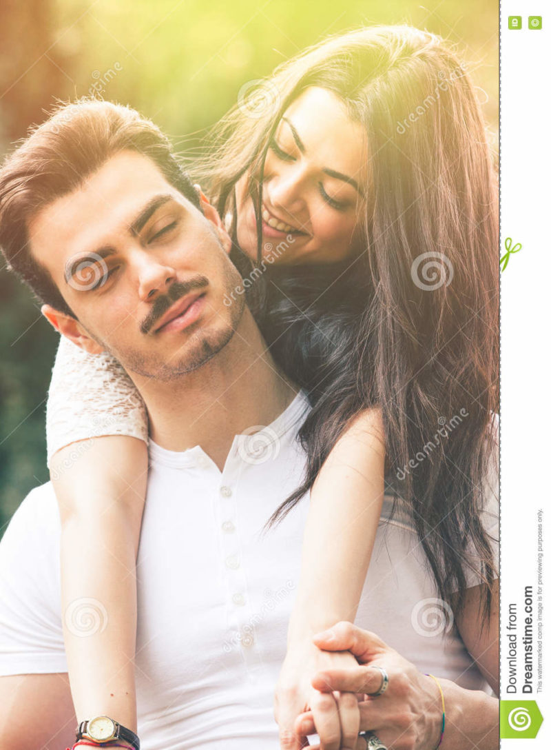 Passion and harmony. Relationship. Love and happiness. Passion and harmony. Relationship. Love and happiness. A smiling beautiful young women embracing her men from behind. Between the two there is a great harmony and joy. The men has a mustache and his eyes closed. Romantic atmosphere and bright outdoors in a natural park.