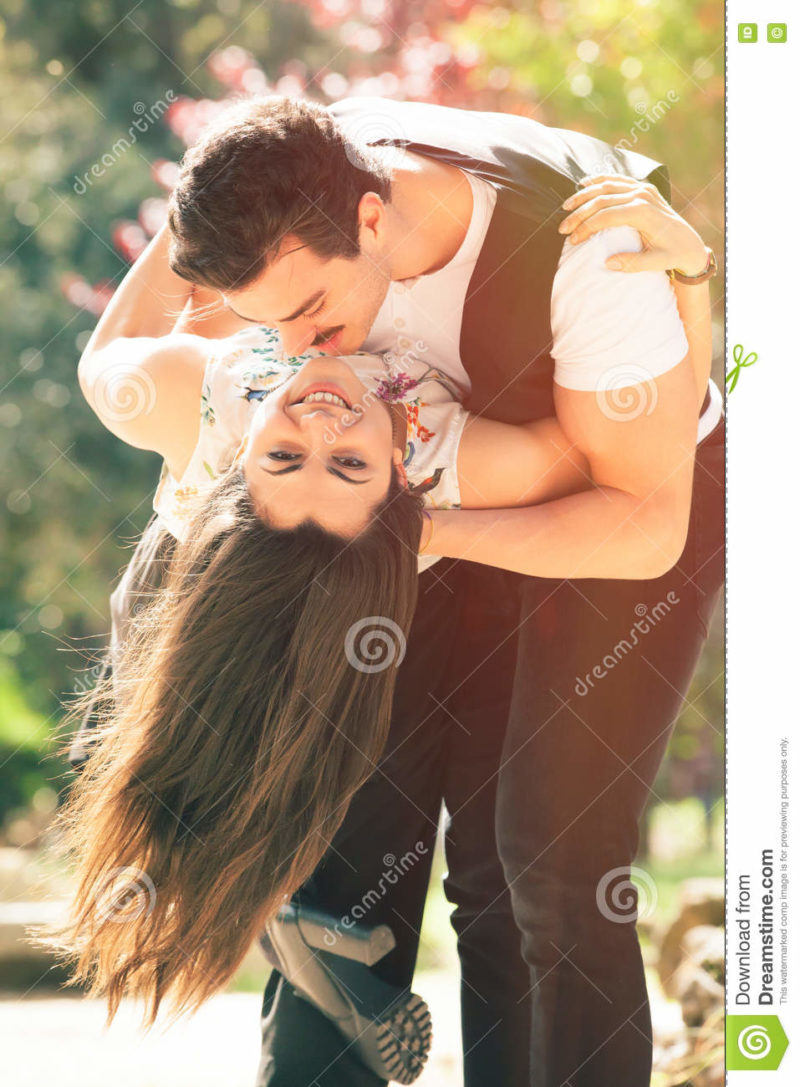 Passionate love, couple romantic relationship. Woman and man Conquer a happy woman. A romantic men embracing a women smiling. Outdoors with trees and flowers in the background. Spring and feelings.