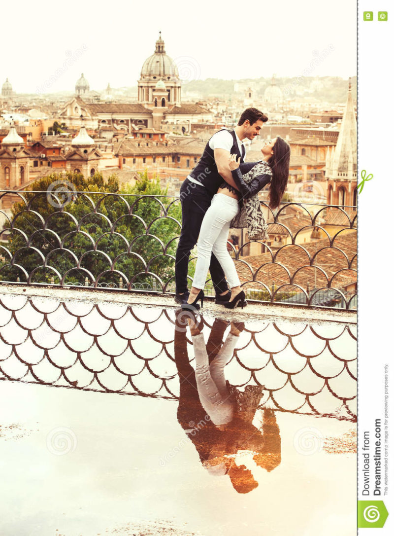 Romantic couple in Rome city, Italy. Loving relationship. Passion and love A beautiful pair embrace on a terrace with a reflection in a puddle. Behind them the historical and ancient city of Rome, Italy. Love, passionate affair, youth and genuine love concept.