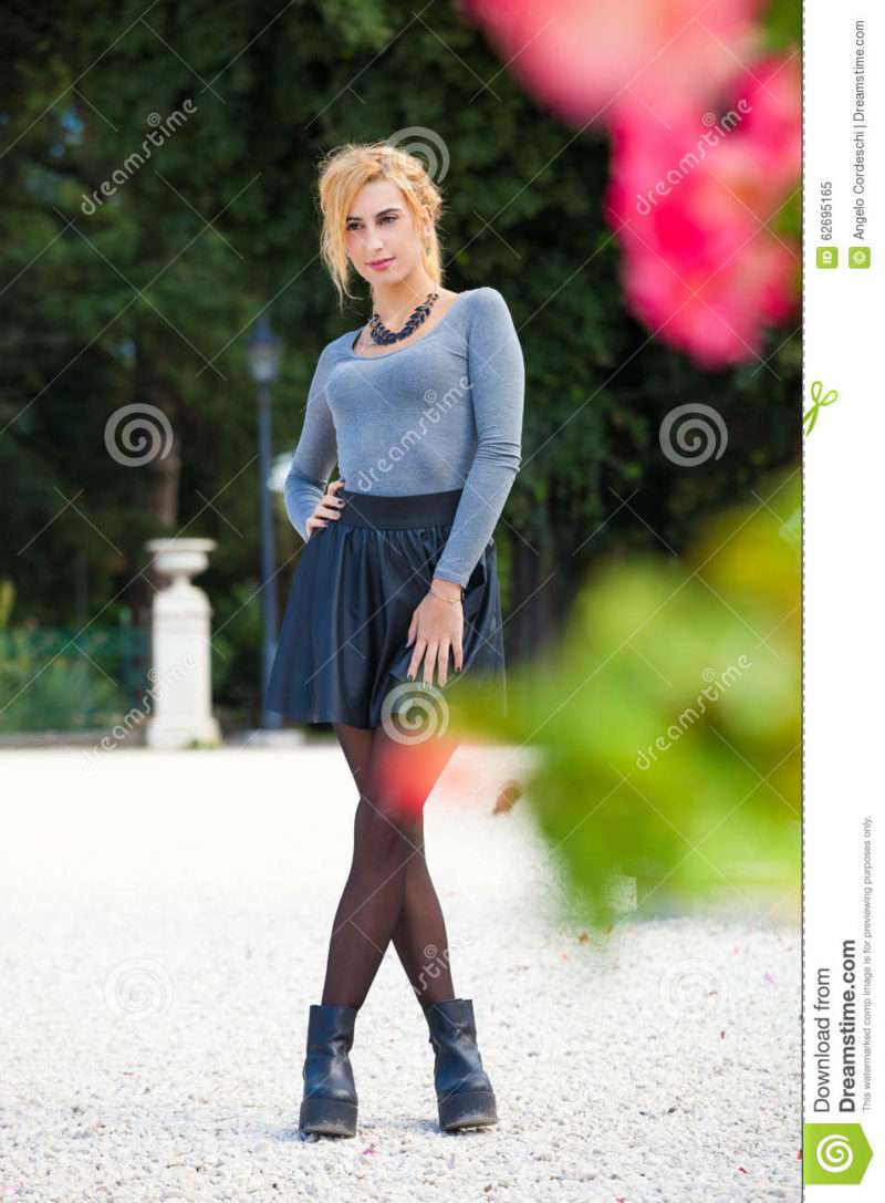 Sweet blond girl outdoors. Natural spring. Sweet blond girl outdoors. Natural spring. A young woman outdoors in a park with flowers and vegetation. Youth apparel and legs crossed.