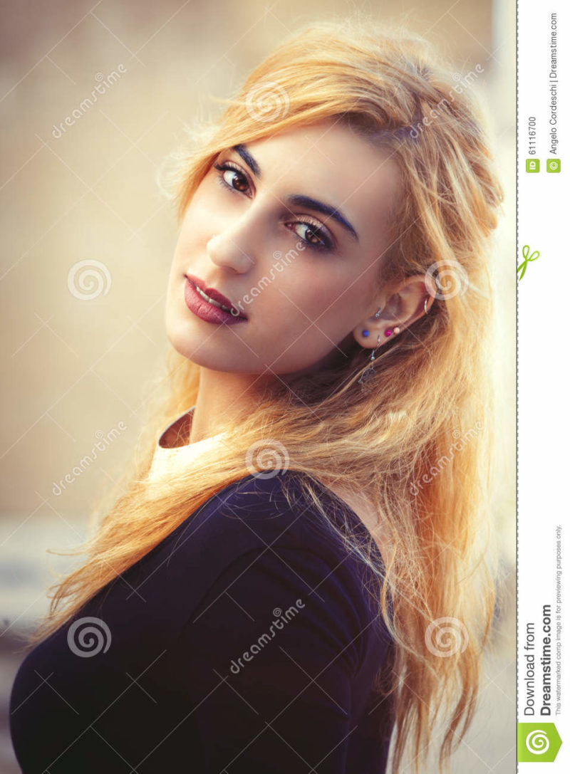 Sweet young blonde girl. Youthful fine beauty. Emotional pose Portrait of a beautiful young Italian girl. Bright eyes and soft colors. Love and romance concept.