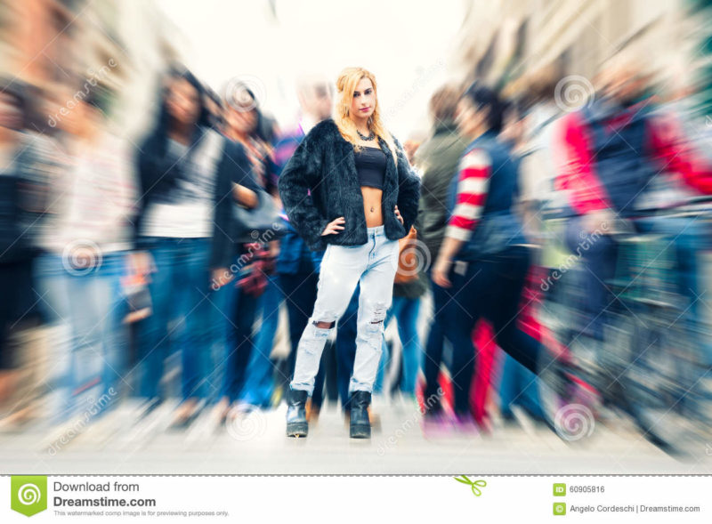 Teen blonde girl in the crowd city. Urban street city life A beautiful young blonde girl in the crowd in the city. with motion zoom blur. Casual youth clothing. Location: Rome, Italy