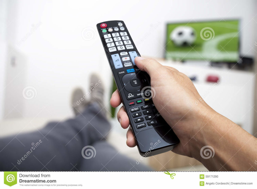 Watching TV. Remote control in hand. Football. Watching football on TV. Remote control in hand. Man lying on the couch watching TV.