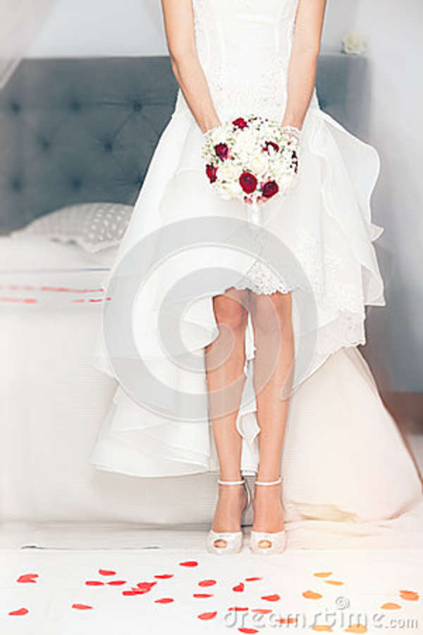 Marry, marriage. Bride at home. Bridal bed. Figure of a woman with a bouquet of flowers in her hand in front of the bridal bed in the bedroom. Rose petals on the floor to the ground
