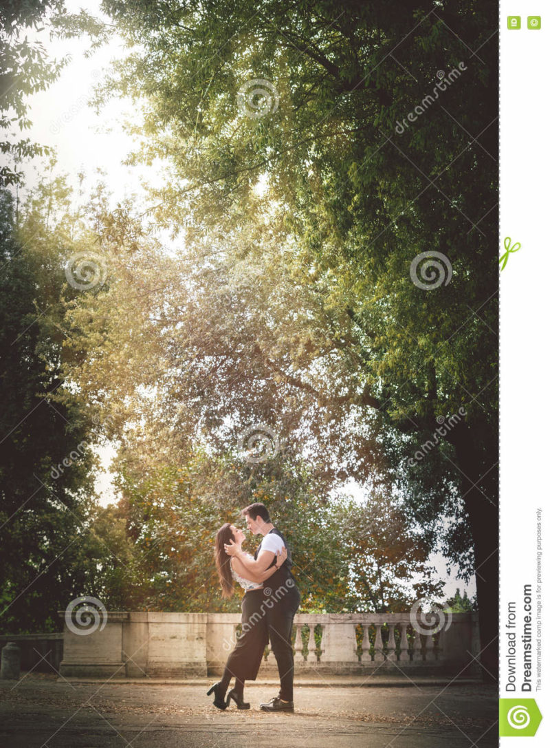 Young couple passion and love outdoor. Trees and nature. Natural love A beautiful young couple, men and woman, close to each other in a tight embrace. Love and deep passion. Feelings and relationship. The two are standing on a street with thick trees. A shaft of sunlight illuminates the scene.