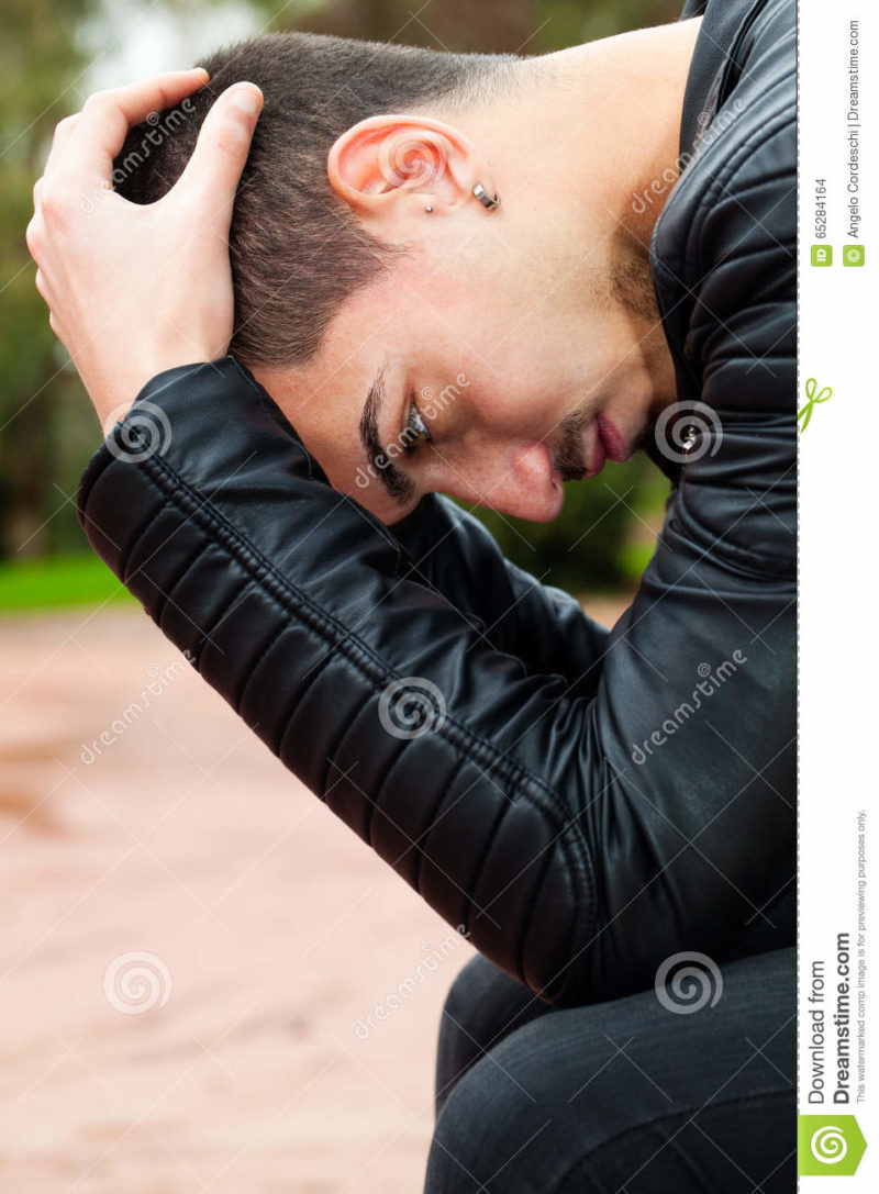 Young man with problems. Desperate men. Close-up image of a handsome young man with hands on head. The boy is thinking of his small and big problems. Concept of anxiety, fear and emotional reaction.