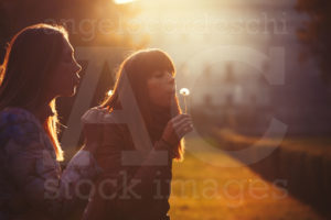Two Young Women Taking And Blowing A Dandelion Flower Warm Lighting And Intense Sunset