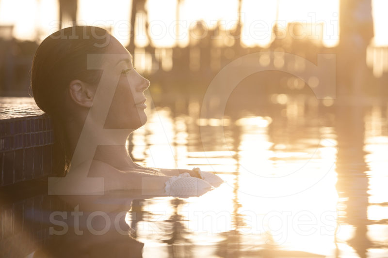 Woman Relaxing By The Pool At Sunset