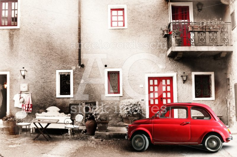 An Old Italian House With A Small Subcompact Old Red Car. Vintag Angelo Cordeschi