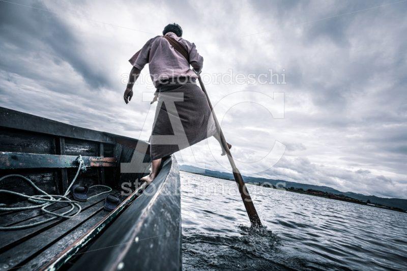Burmese Fisherman Standing On His Boat Rowing With The Oar With Angelo Cordeschi