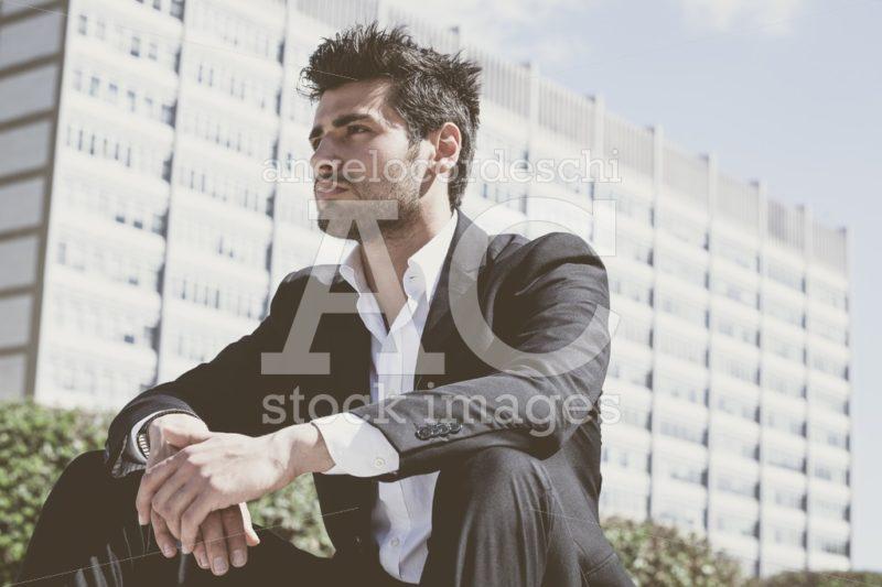 Confident handsome man sitting outdoor. Modern building behind. - Angelo Cordeschi
