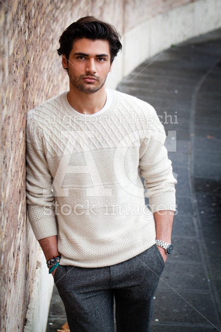 Handsome Young Man Leaning On A Long Wall Outdoors, Hands In His Angelo Cordeschi