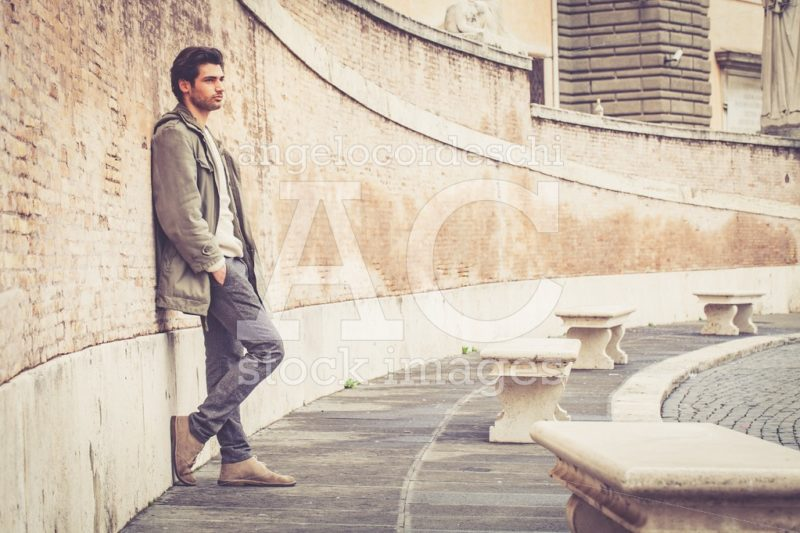 Handsome Young Man Leaning On A Long Wall Outdoors. Casual Cloth Angelo Cordeschi