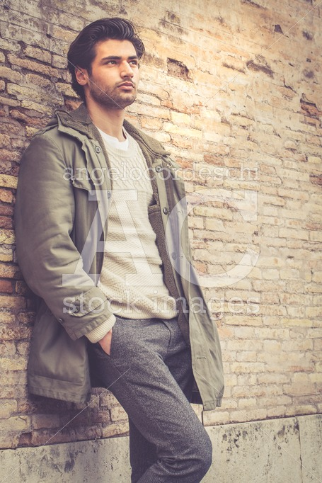 Handsome Young Man Leaning On A Wall Outdoors. Casual Clothes, W Angelo Cordeschi