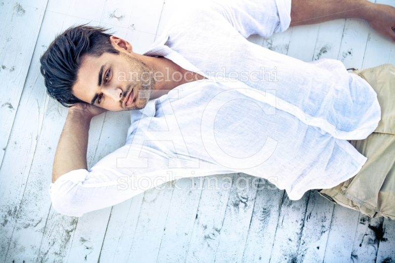 Handsome Young Man Lying On A White Wooden Surface. Angelo Cordeschi