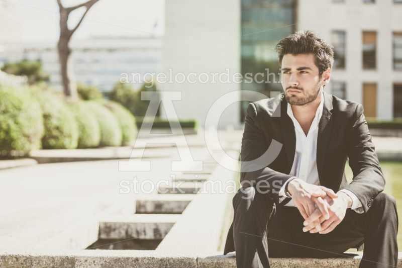 Handsome young man sitting in the city. Relaxed thinking with his arms on her legs. - Angelo Cordeschi