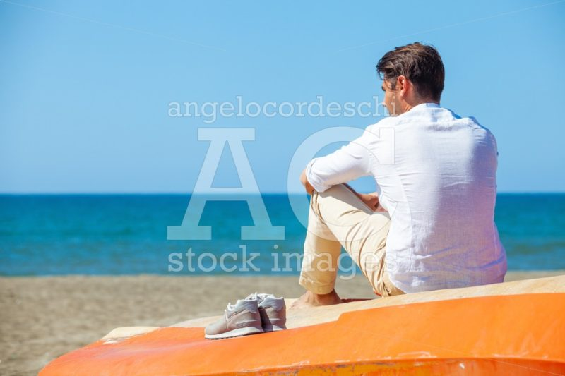 Lonely Man On The Beach Above A Boat Looking At The Sea. Angelo Cordeschi