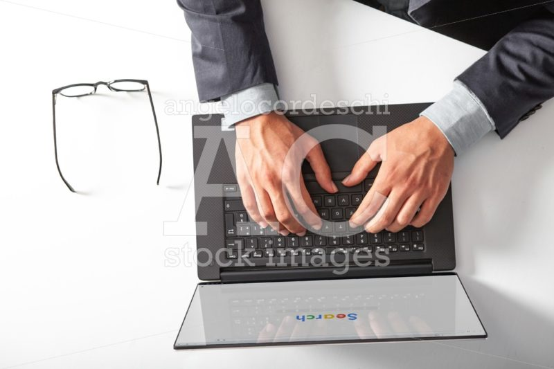 Man With Laptop Typing On The Keyboard Doing A Search. Angelo Cordeschi