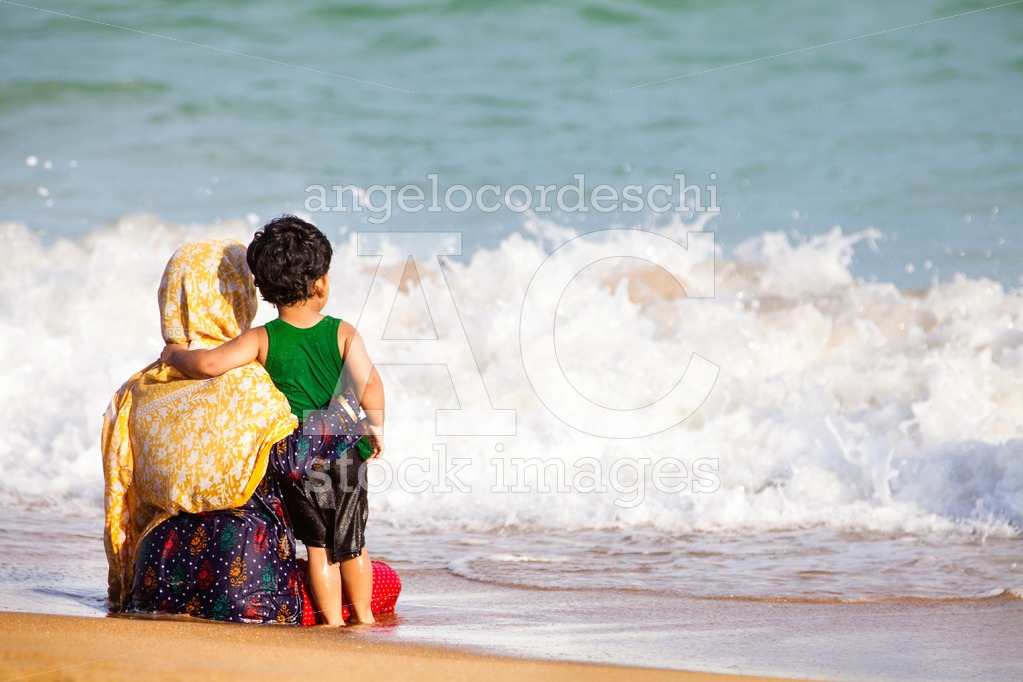 Mother And Her Little Are Sitting Embraced On The Seashore. Angelo Cordeschi