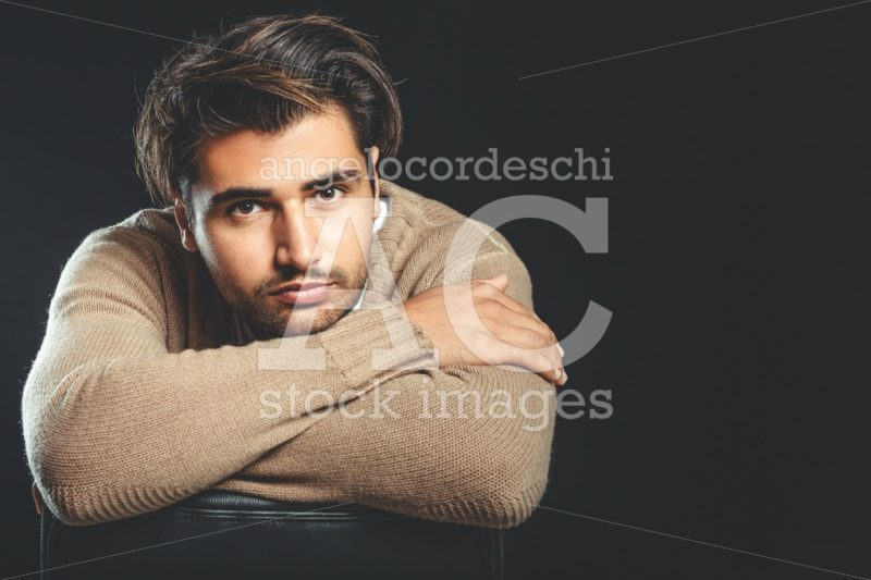 Pensive Young Man With Folded Arms In Studio. Black Faded Backgr Angelo Cordeschi