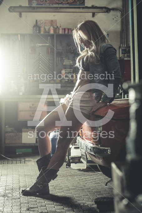 Sensual and sexy woman in front garage sitting on an old vintage - Angelo Cordeschi