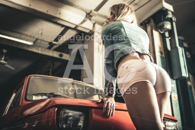 Sexy woman buttocks in shorts. Garage in front of an old vintage car. - Angelo Cordeschi