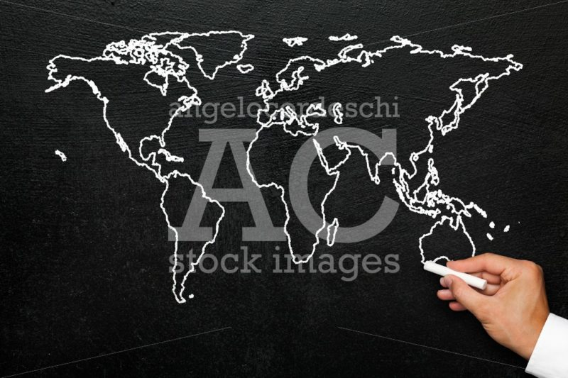 World map on blackboard. A hand draws a stylized globe map of th - Angelo Cordeschi