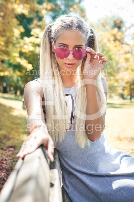 Young Blonde Woman With Colorful Sunglasses Sitting On A Bench O Angelo Cordeschi