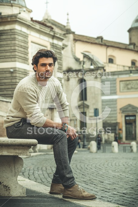 Young Man Sitting On A Marble Bench In The Street In The City. S Angelo Cordeschi